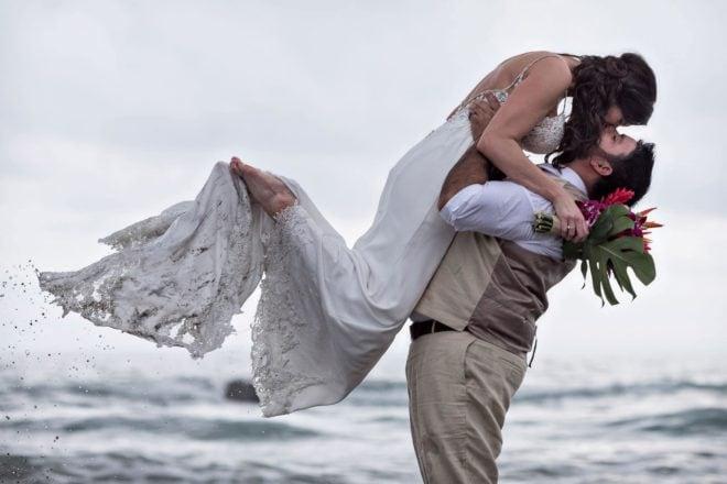 Groom tosses bride in the air as ocean water trickles off her toes