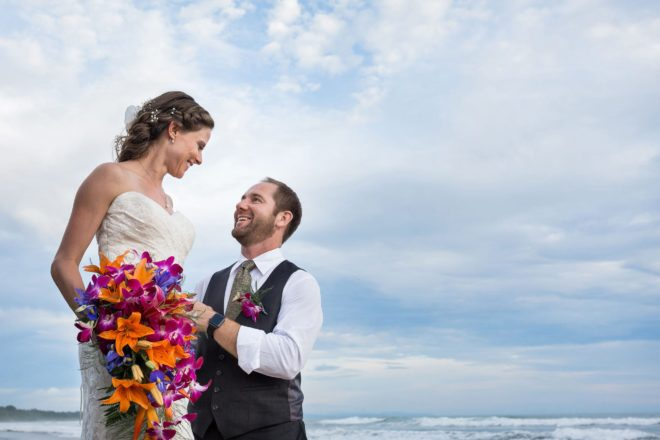 Bride and groom gazing into each other's eyes on the beach