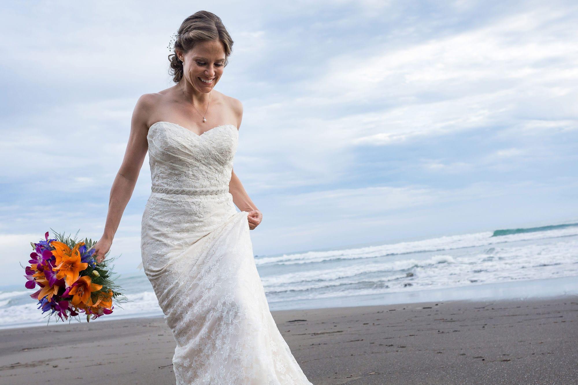The bride on the beach with blue skies peeking through