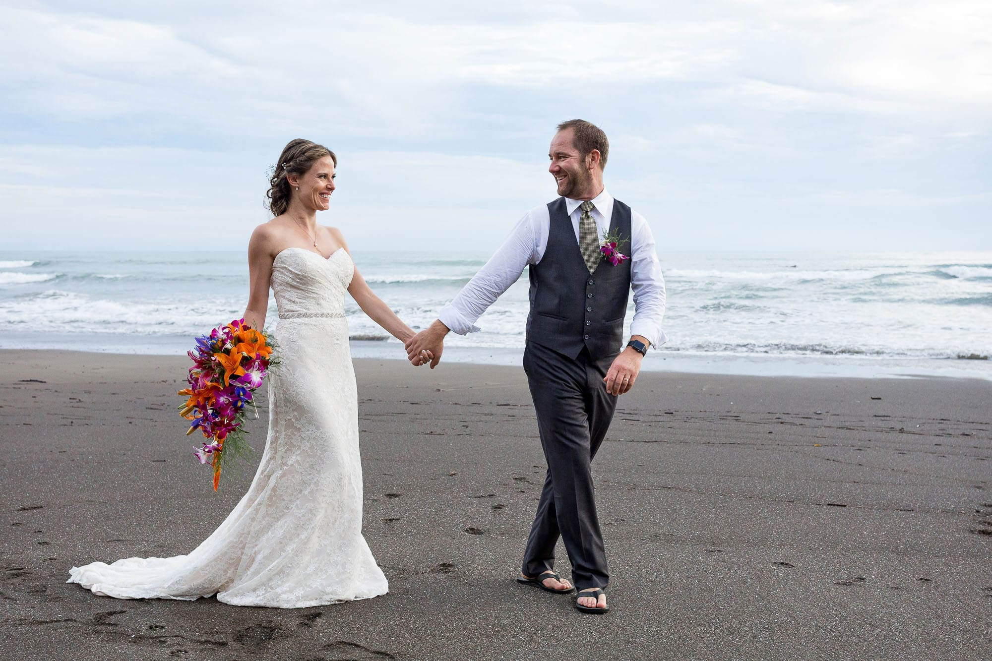 Bride and groom walking on the beach holding hands