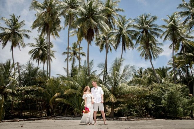 Bride and groom on the beach with lovely palm tree background.