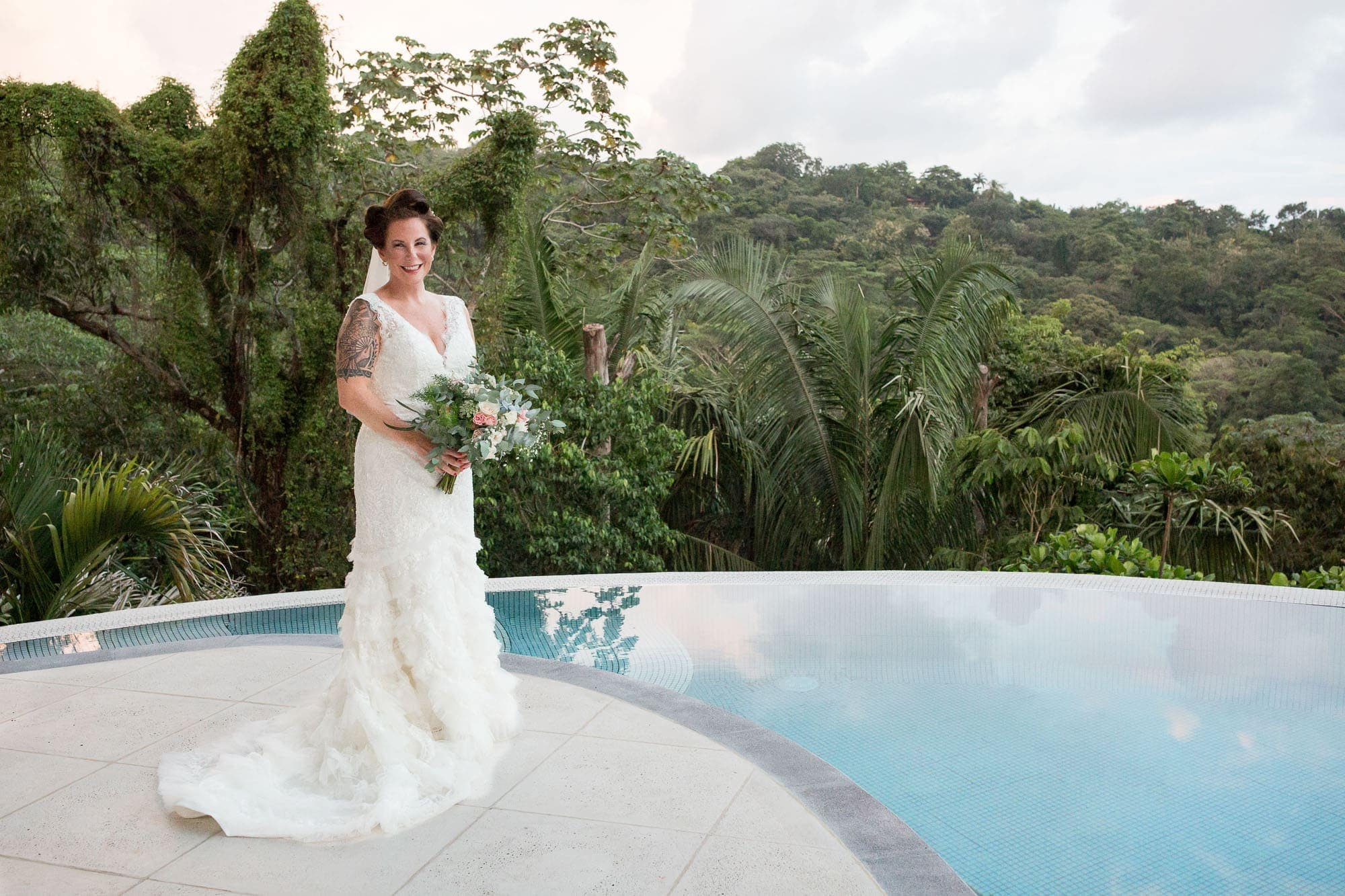 Bride posing by the pool