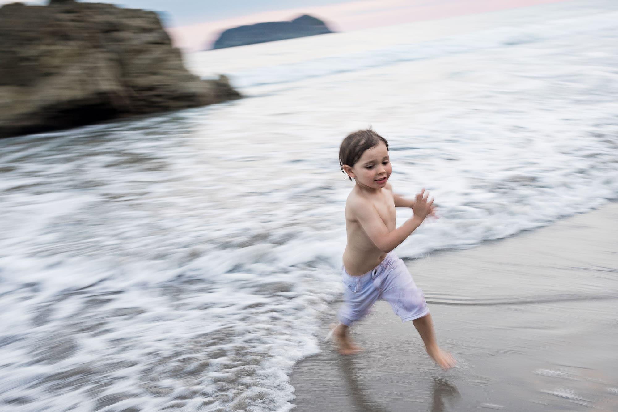 boy running on beach in costa rica