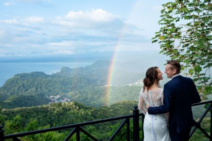 The wedding couple with a rainbow and rainforest and ocean view in Costa Rica