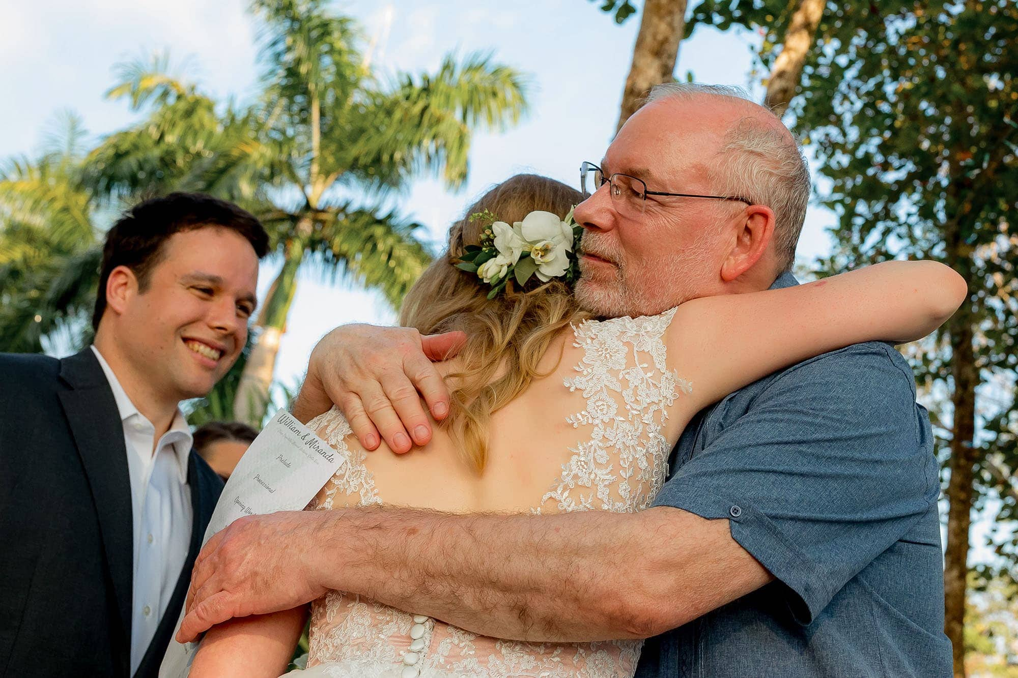 The bride hugging her dad with the groom smiling in the background