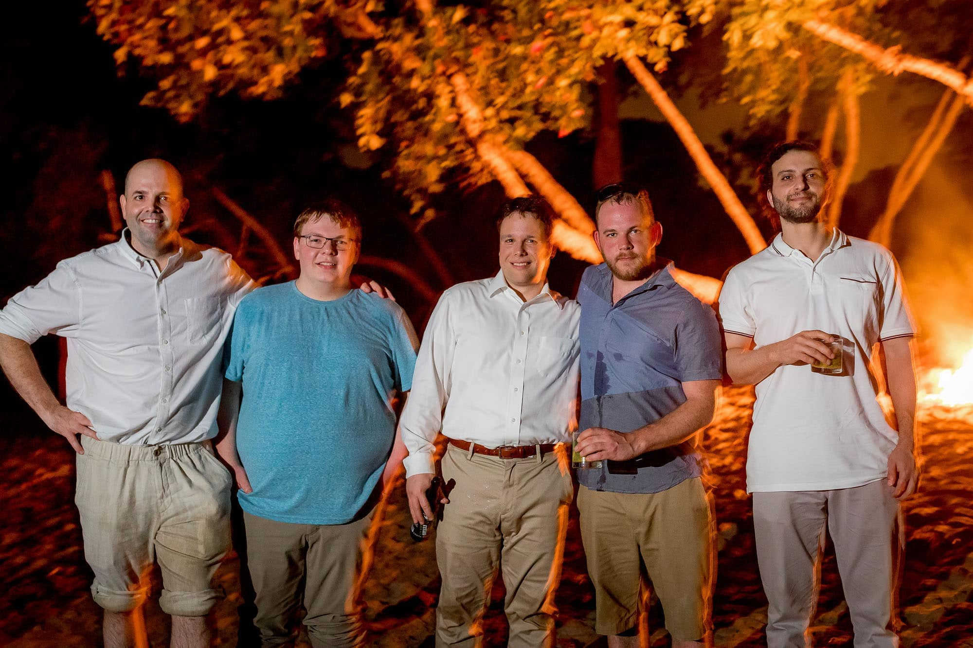 The groom with his buddies in front of the bonfire