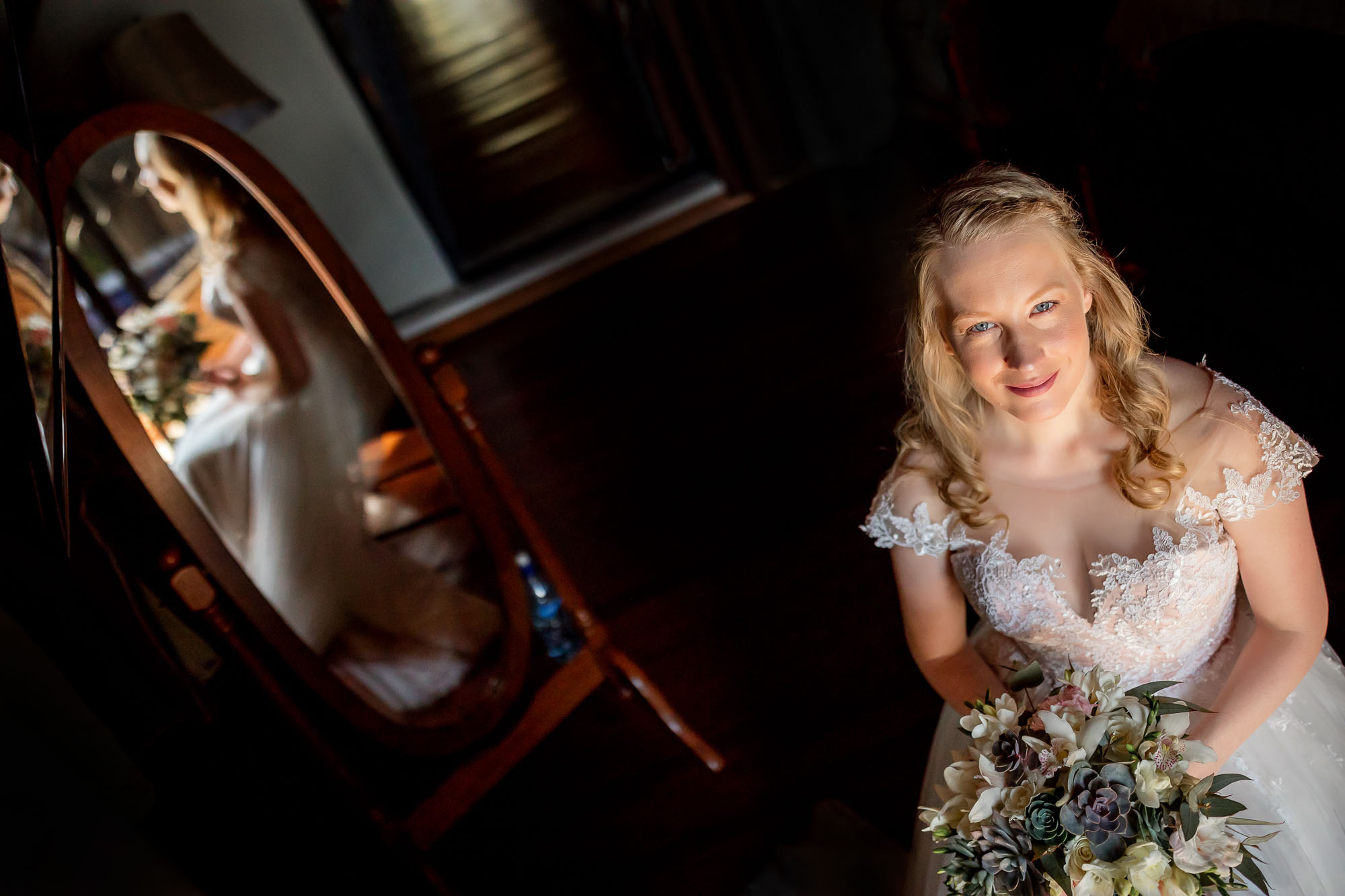 Creative wedding shot from above with the bride reflected in the mirror behind her