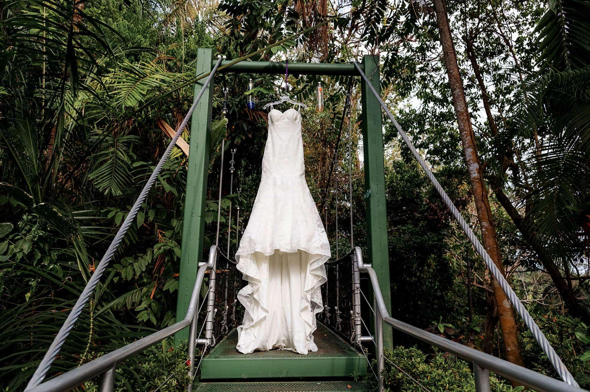 The elegant formal wedding gown hanging in the hanging bridge at Costa Verde