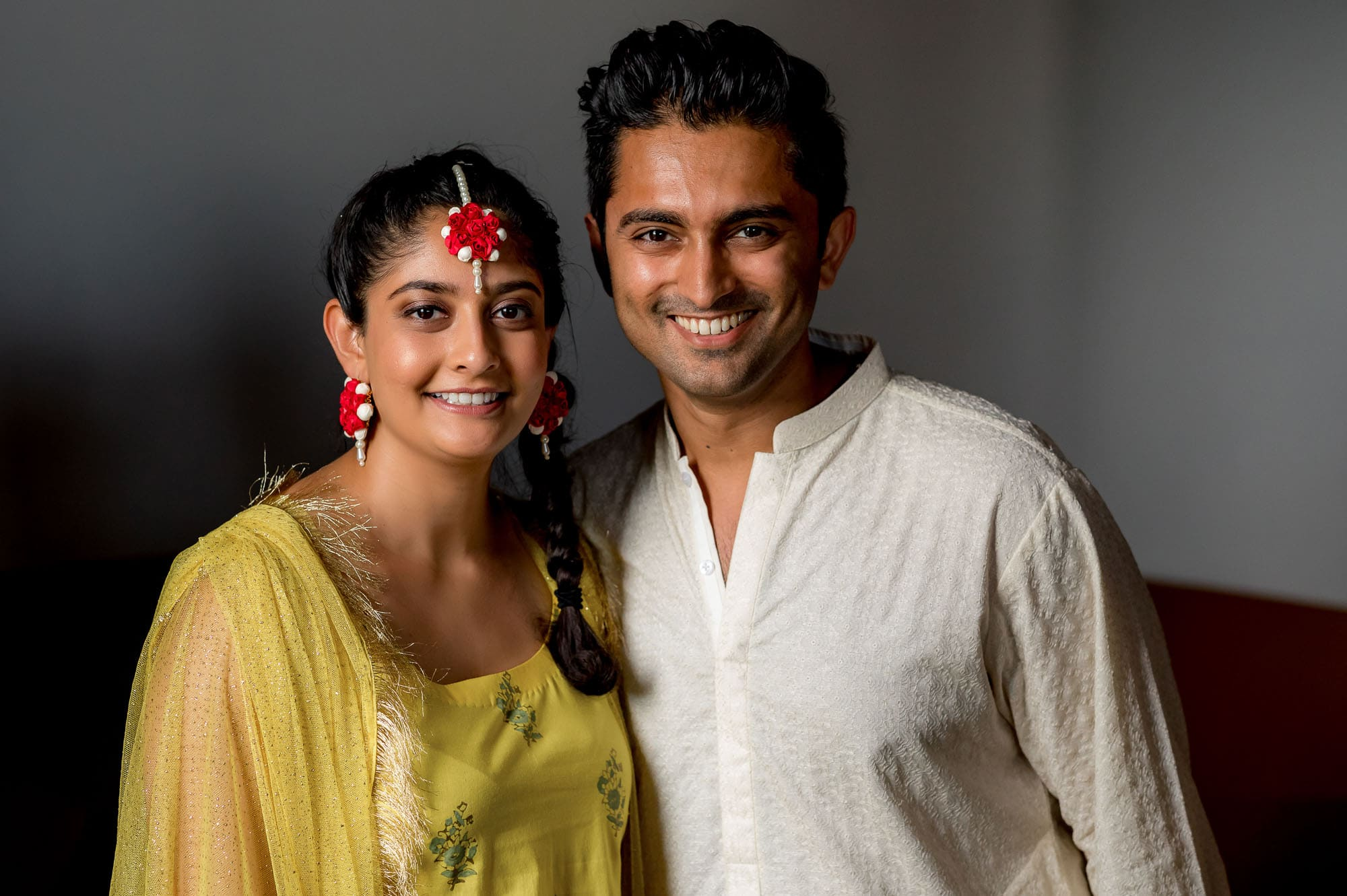 Smiling posed shot of the bride and groom before the Pithi ceremony