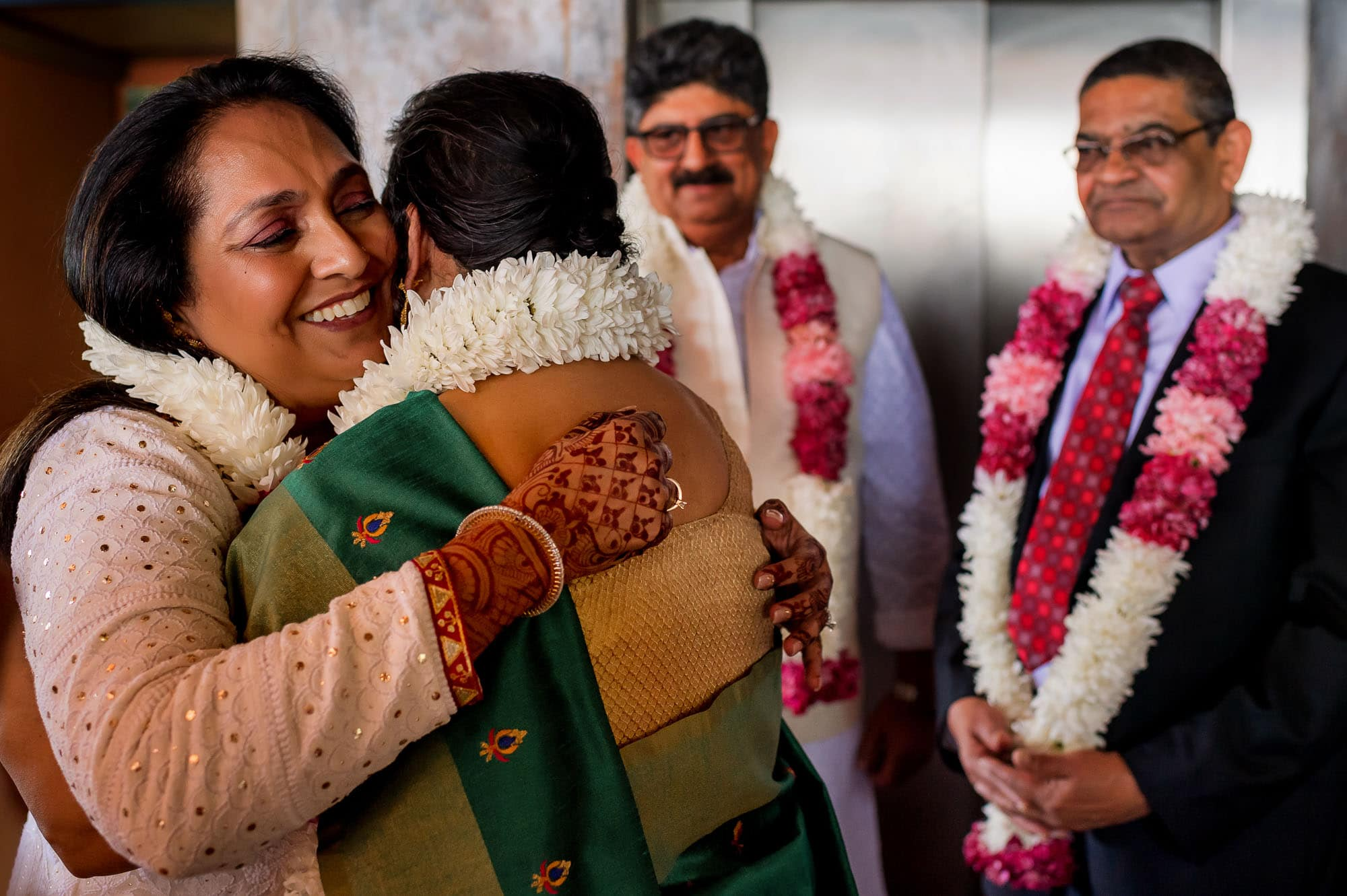 The mothers of the bride and groom share a hug