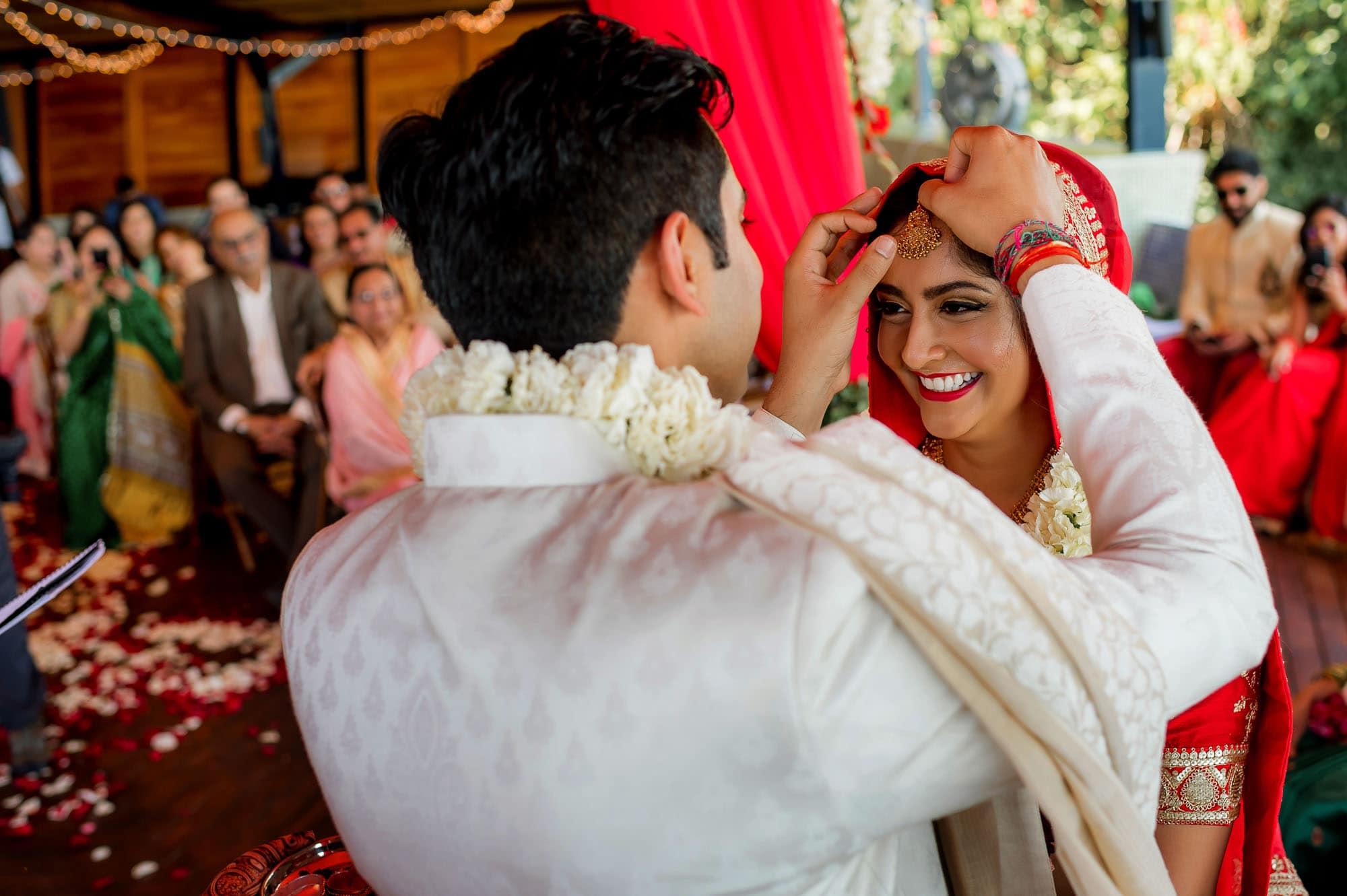 The groom adjusts the bride's headpiece