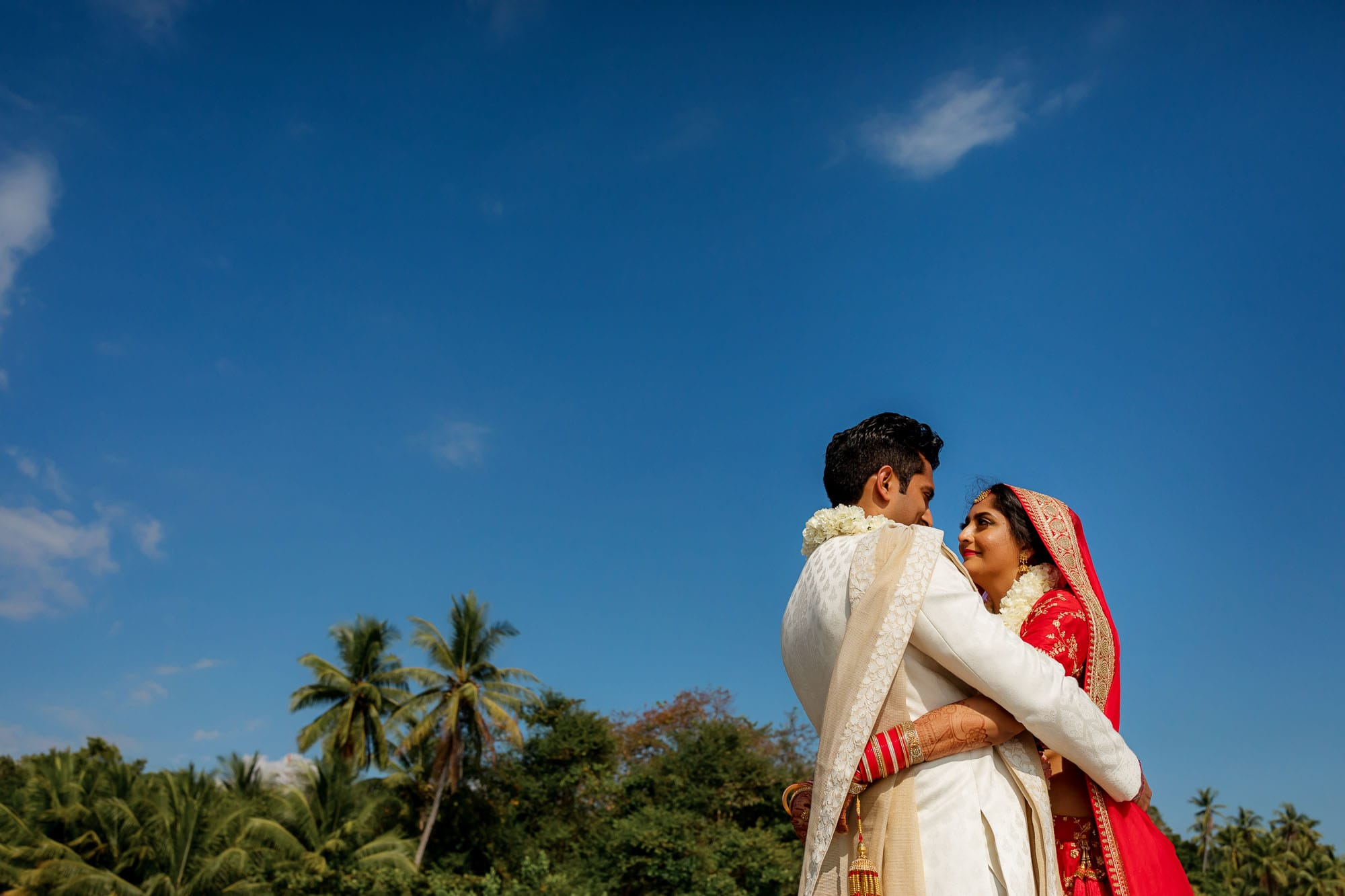 The bride and groom on the beach in traditional Hindu garb