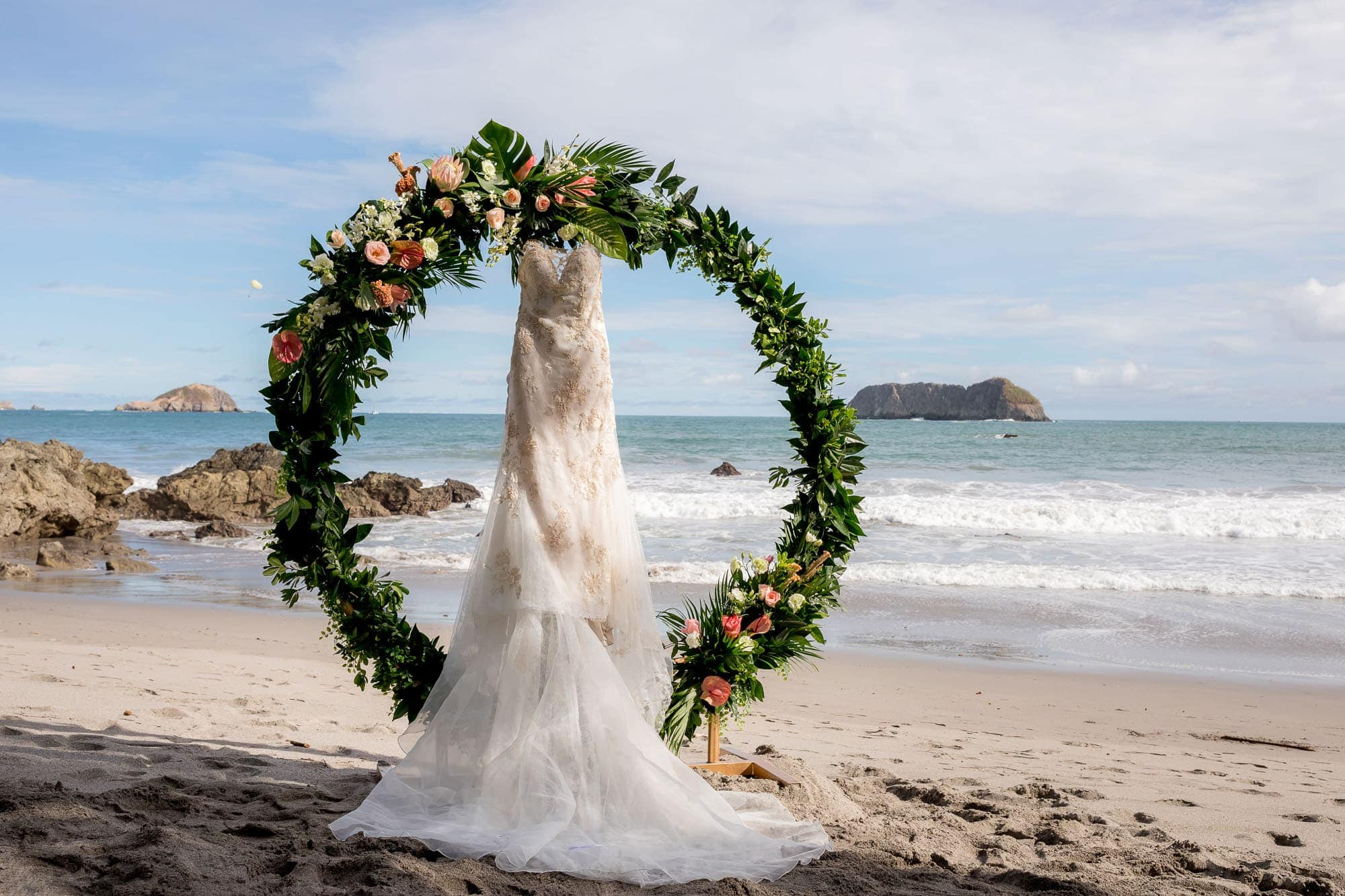 The bride's dress hanging in their circular ceremony arbor