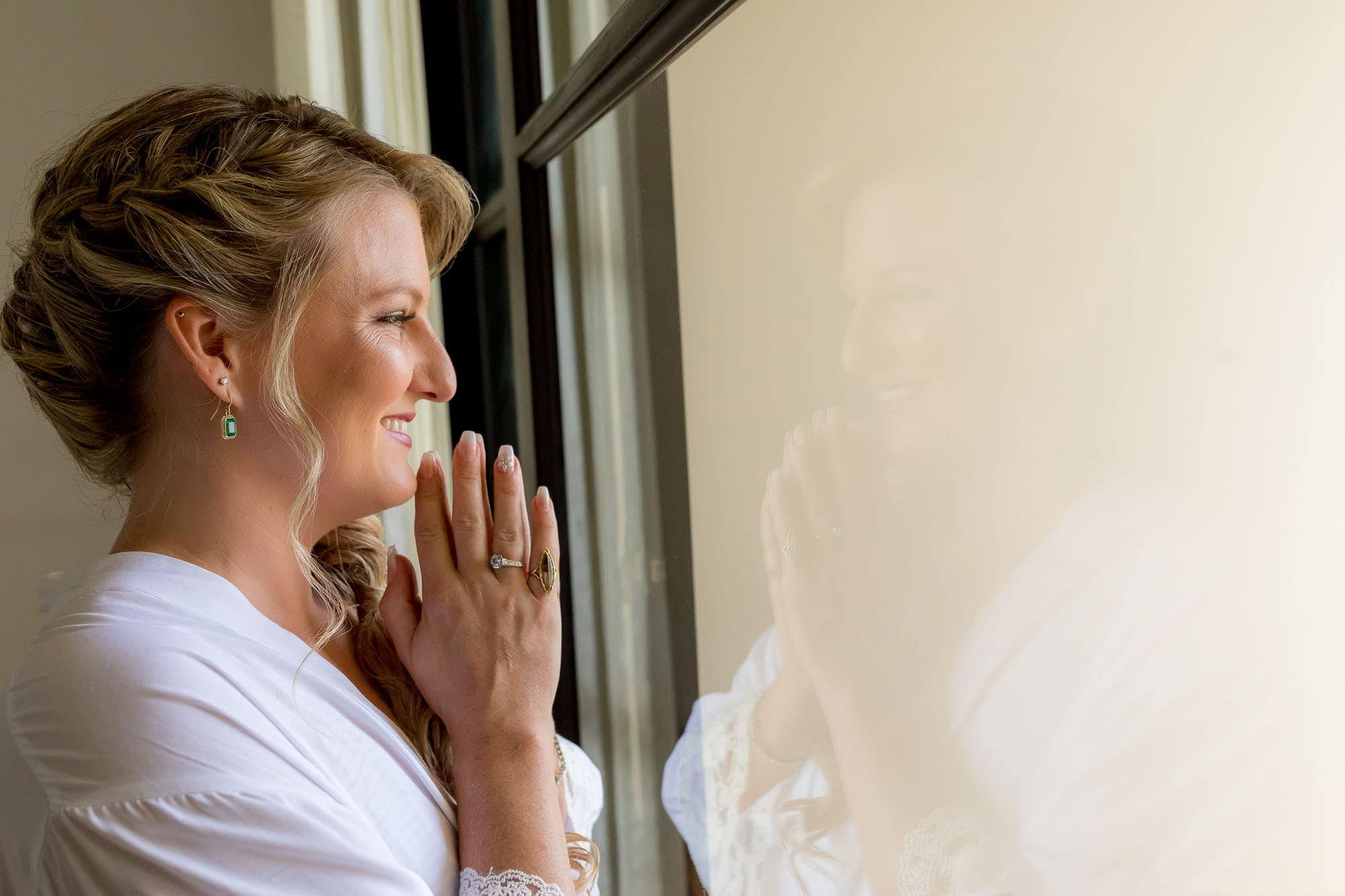 The bride looking out the window before the ceremony and beach wedding reception