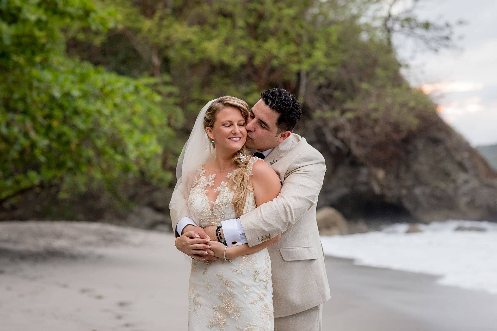 The bride and groom on the beach before the beach wedding reception