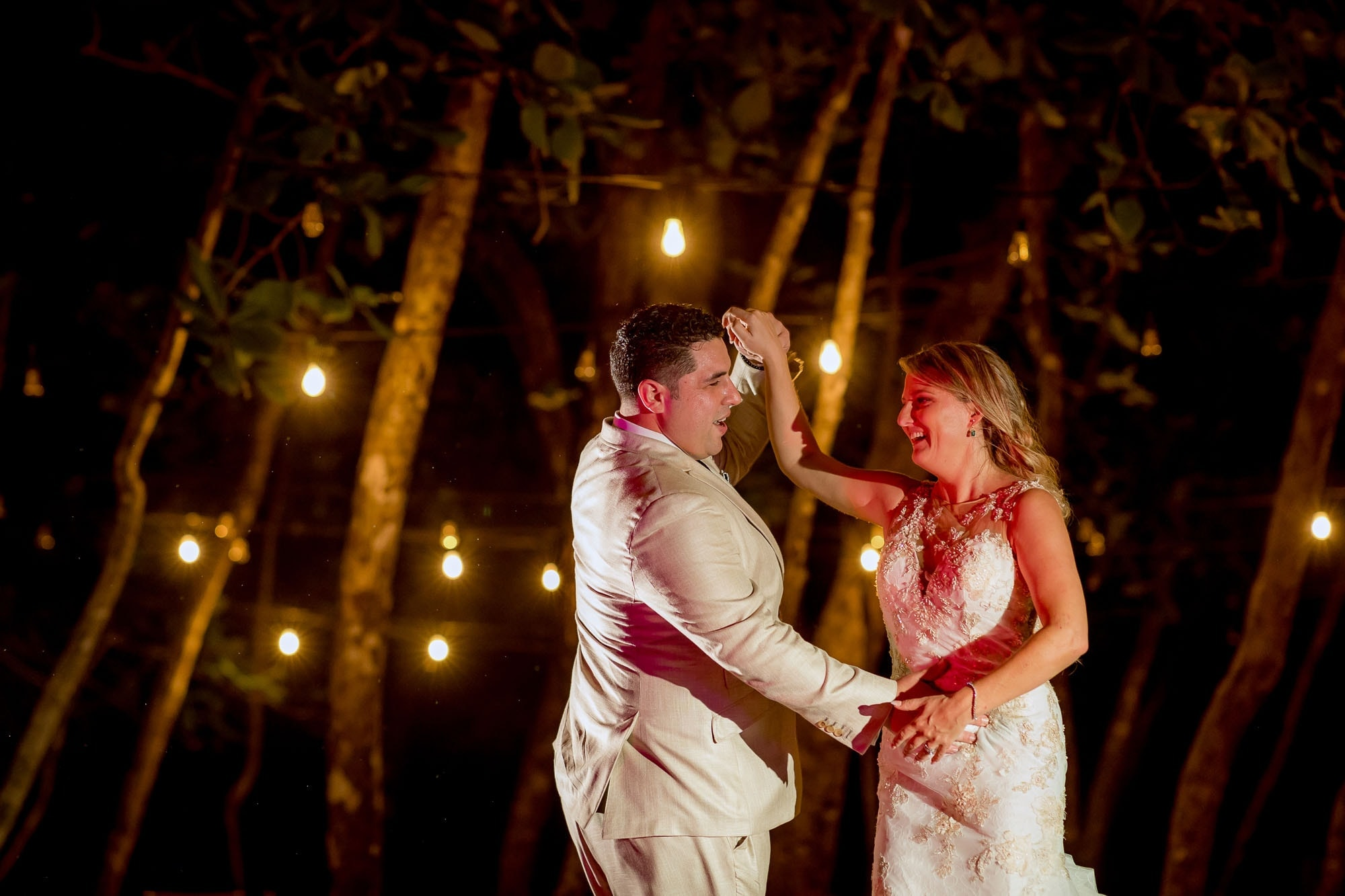 The bride and groom dancing at the beach wedding reception