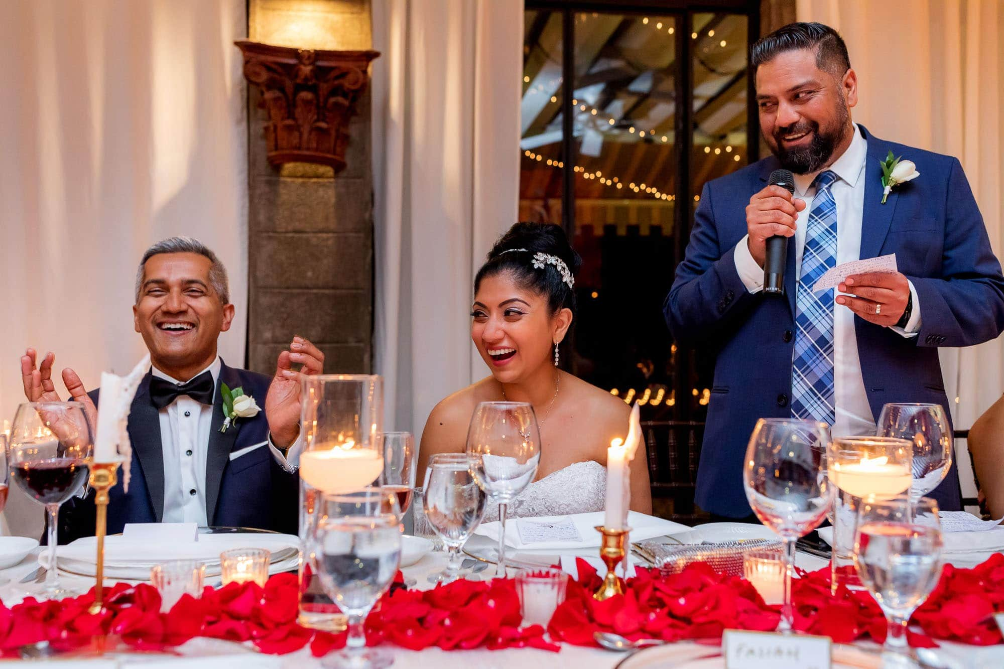 The bride and groom laughing at the best man's toast