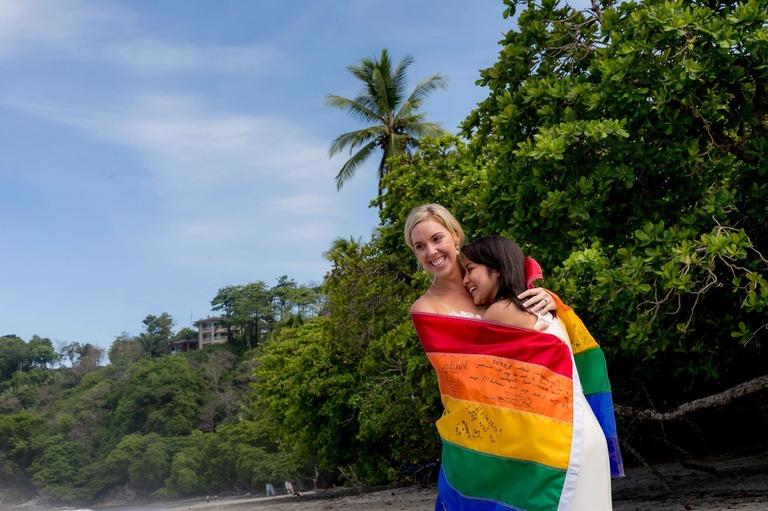 brides with pride flag at wedding