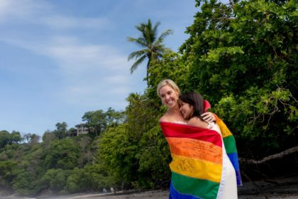 brides with pride flag at wedding