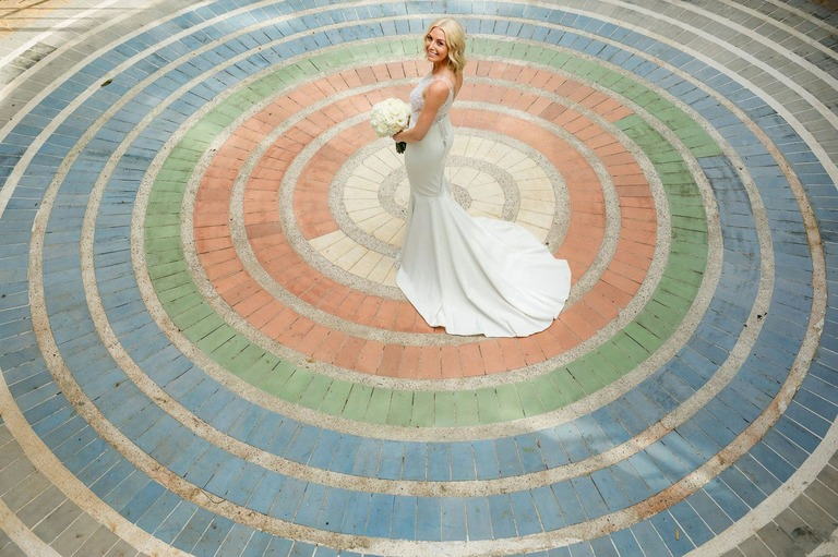The bride at the center of a circular colored brick pattern