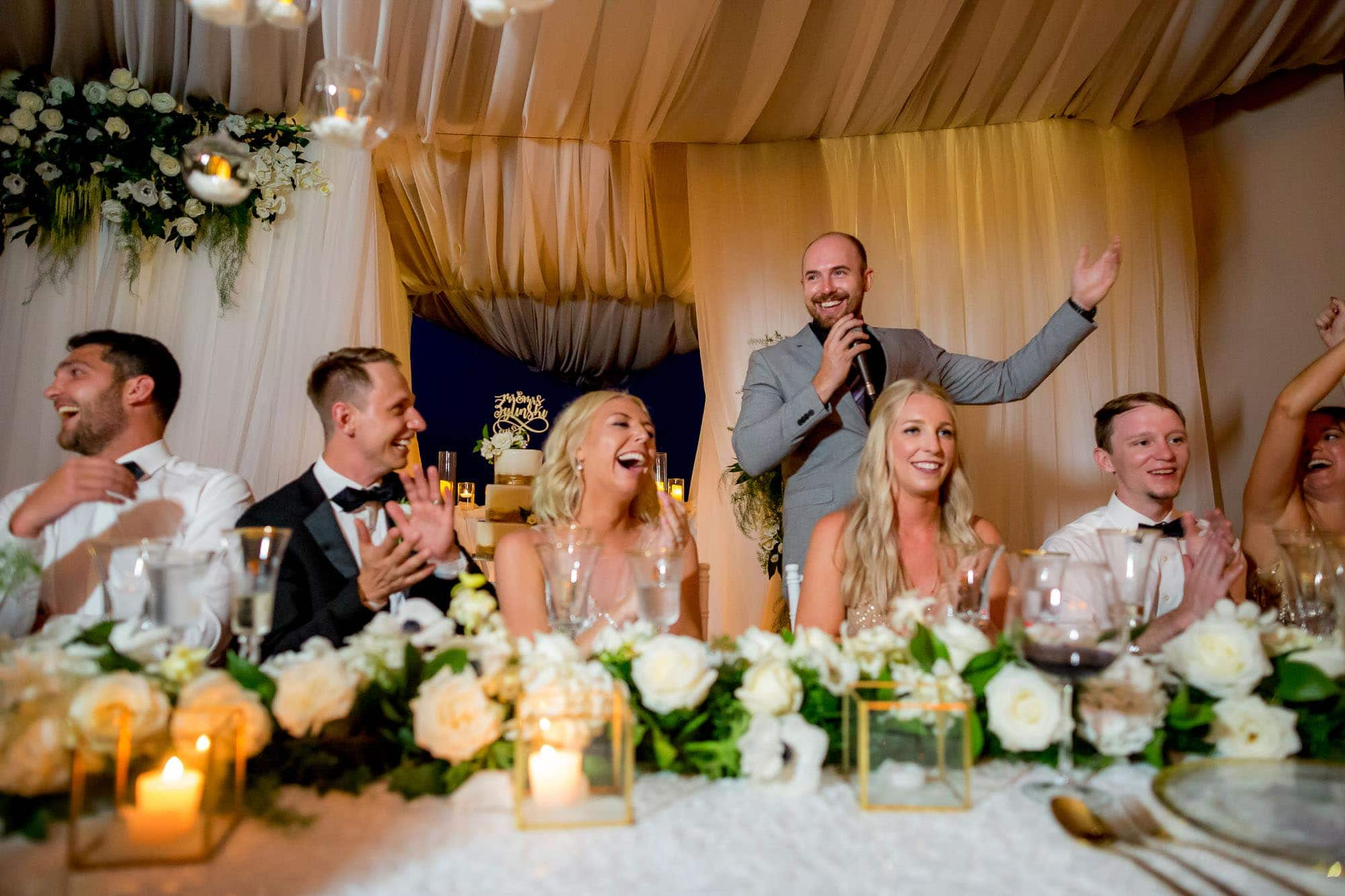 Bride and groom laughing heartily at a speech