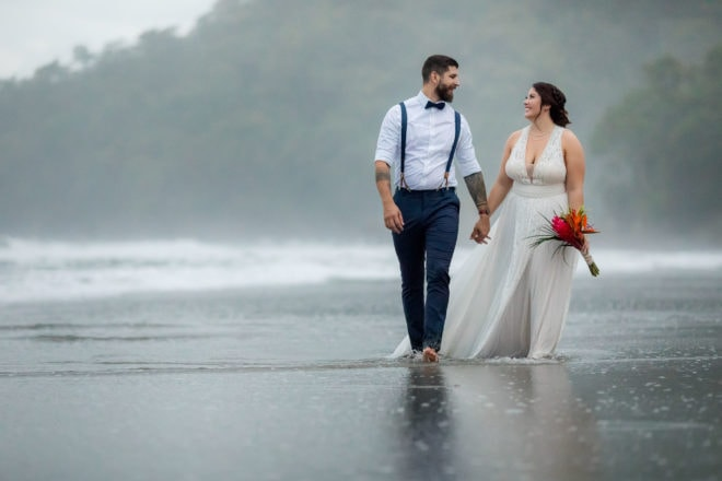 Bride and groom walk along the beach for their elopement wedding