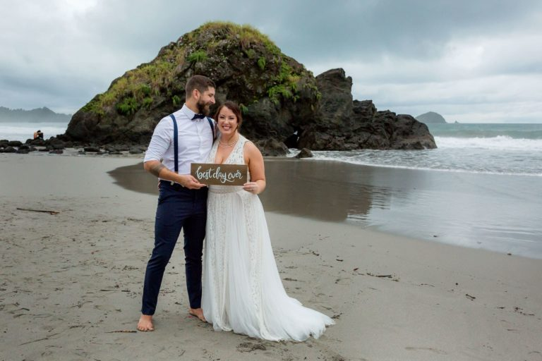"Bride and groom on the beach with sign ""best day ever"""