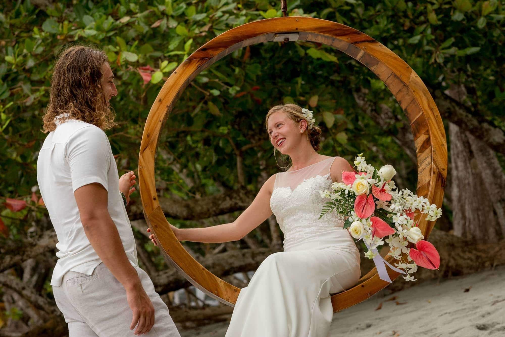Bride seated in a circle swing with groom at her side