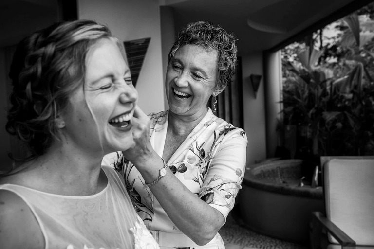 Mom laughing with the bride as she gets ready to get married