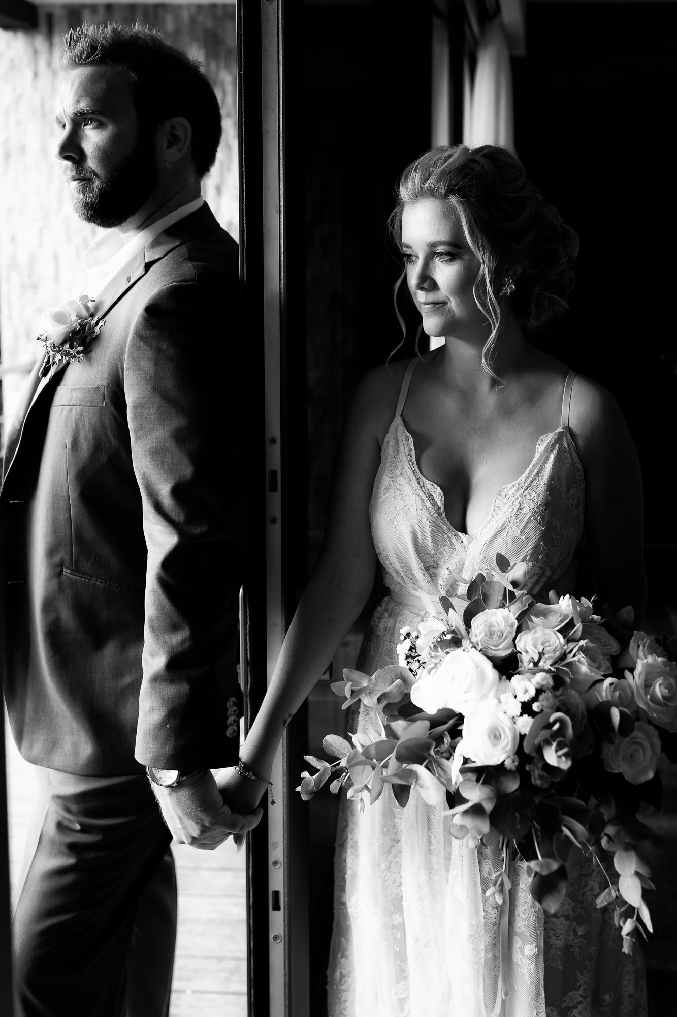 Poignant black and white capture of the bride and groom on either side of a door (they can't see each other yet)