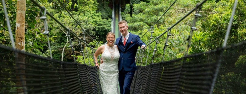Bride and groom on a suspension bridge above the jungle