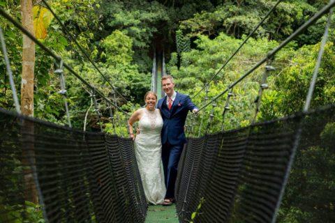 Bride and groom on a suspension bridge above the jungle