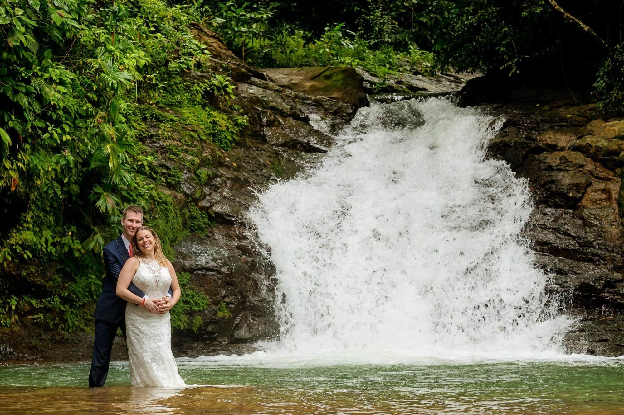 Bride and groom posing off the beaten path in Costa Rica at the base of a waterfall