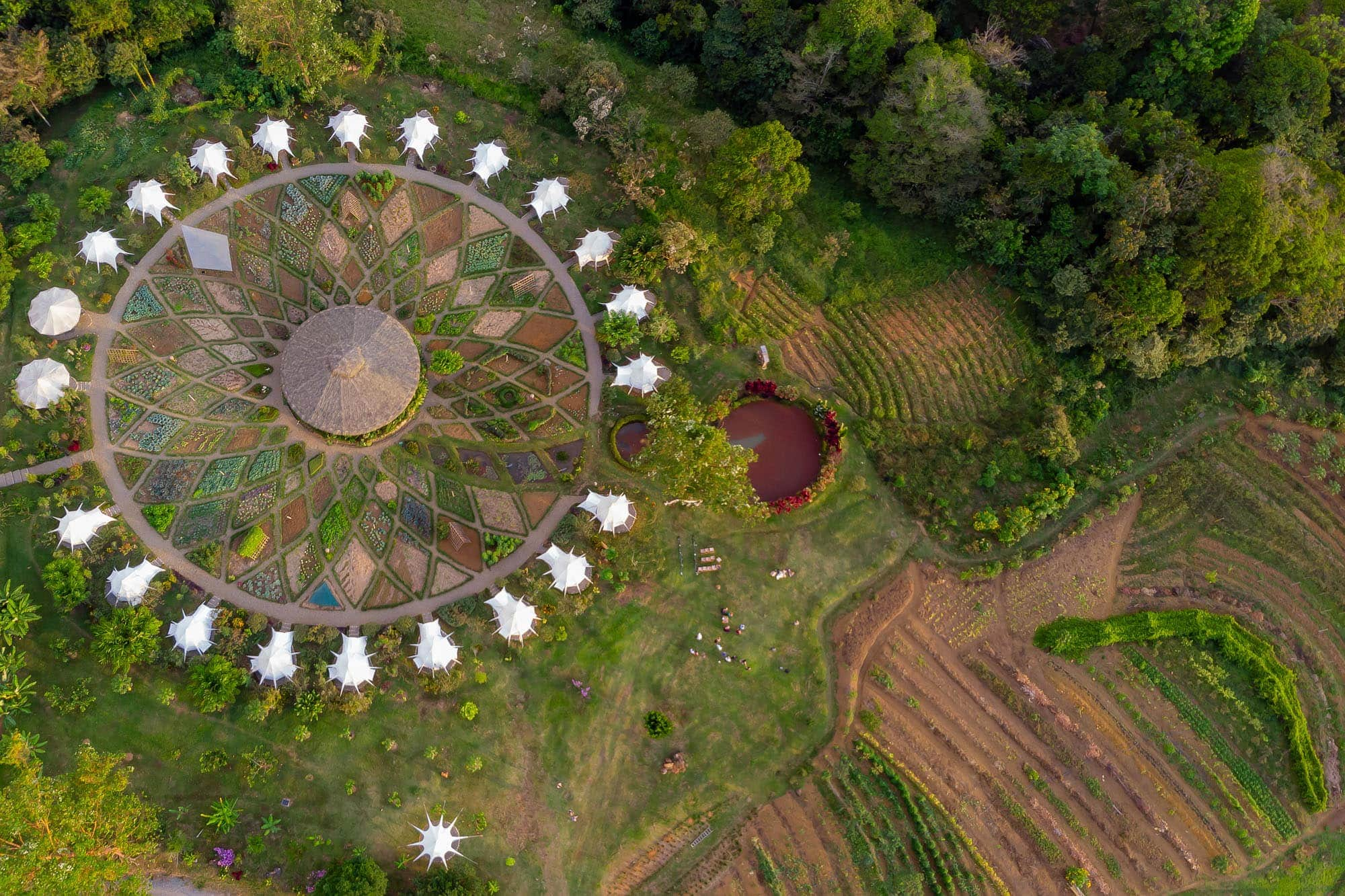 Aerial shot showing the ring of glamping tents and the meticulously organized gardens of Kinkara