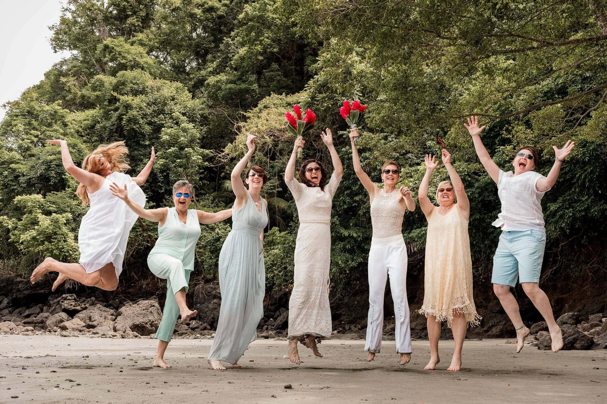 wedding guests jump at beach wedding
