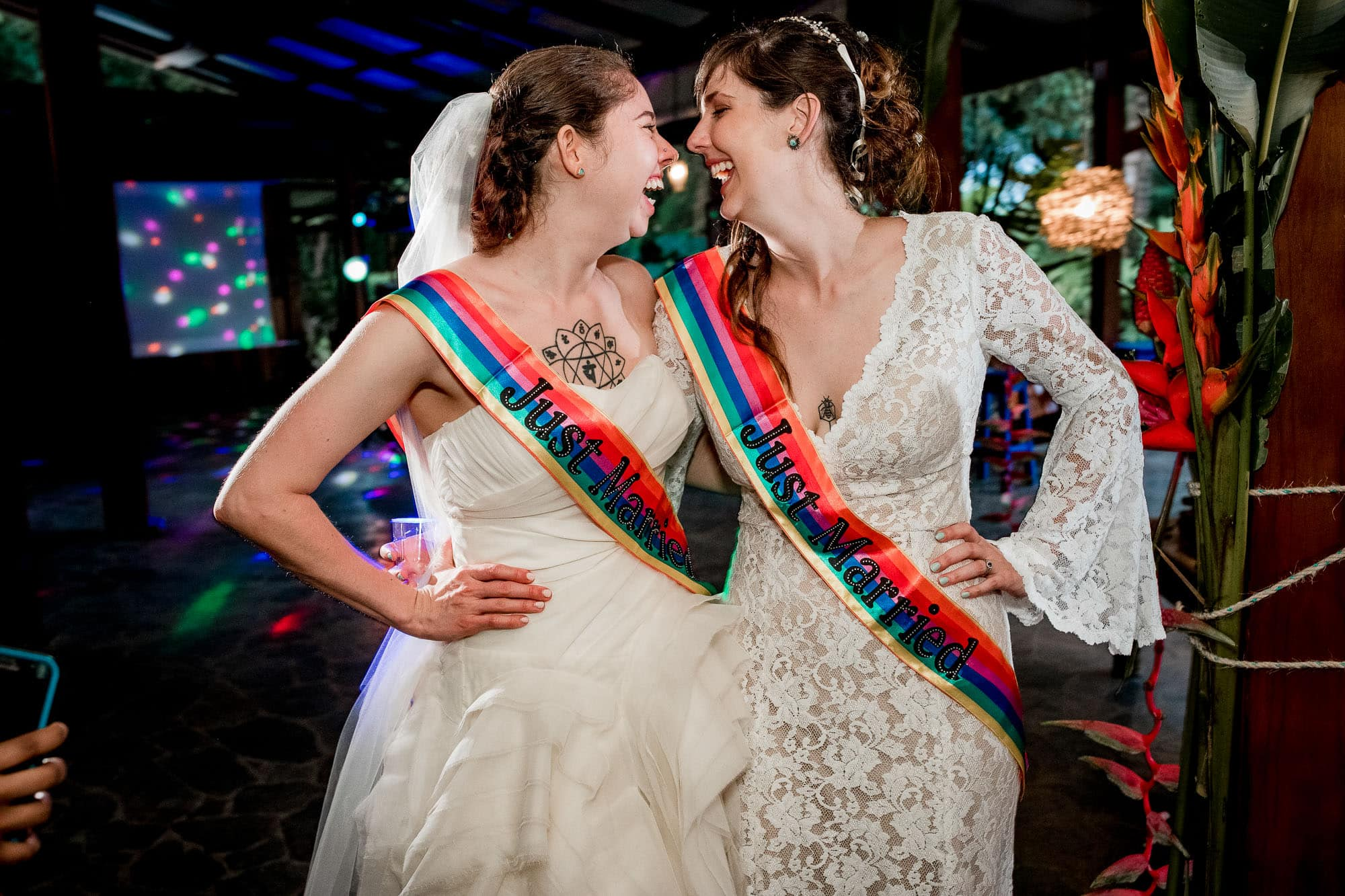 two brides with rainbow sashes