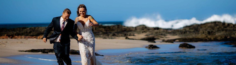 The tattooed bride and groom walking along Langosta Beach
