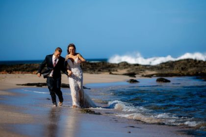 The tattooed bride and groom walking along Langosta Beach