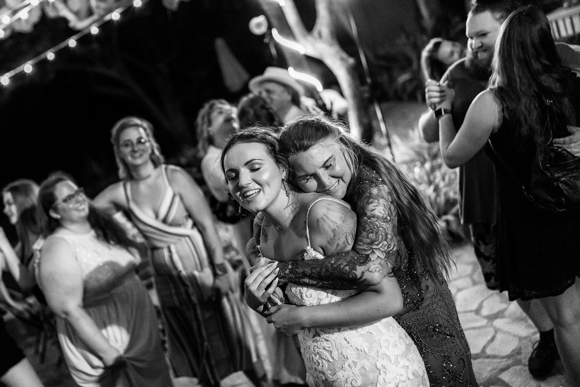 The bride's mother gives her daughter a hug