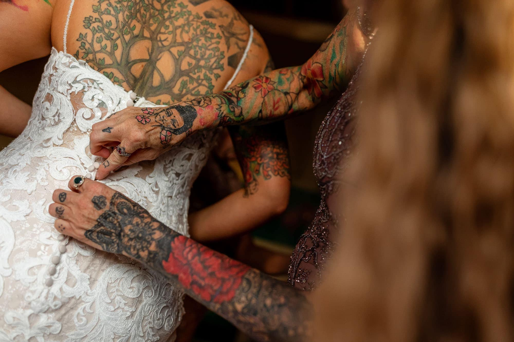 Mother's tattooed arms as she buttons up the back of the tattooed bride's dress