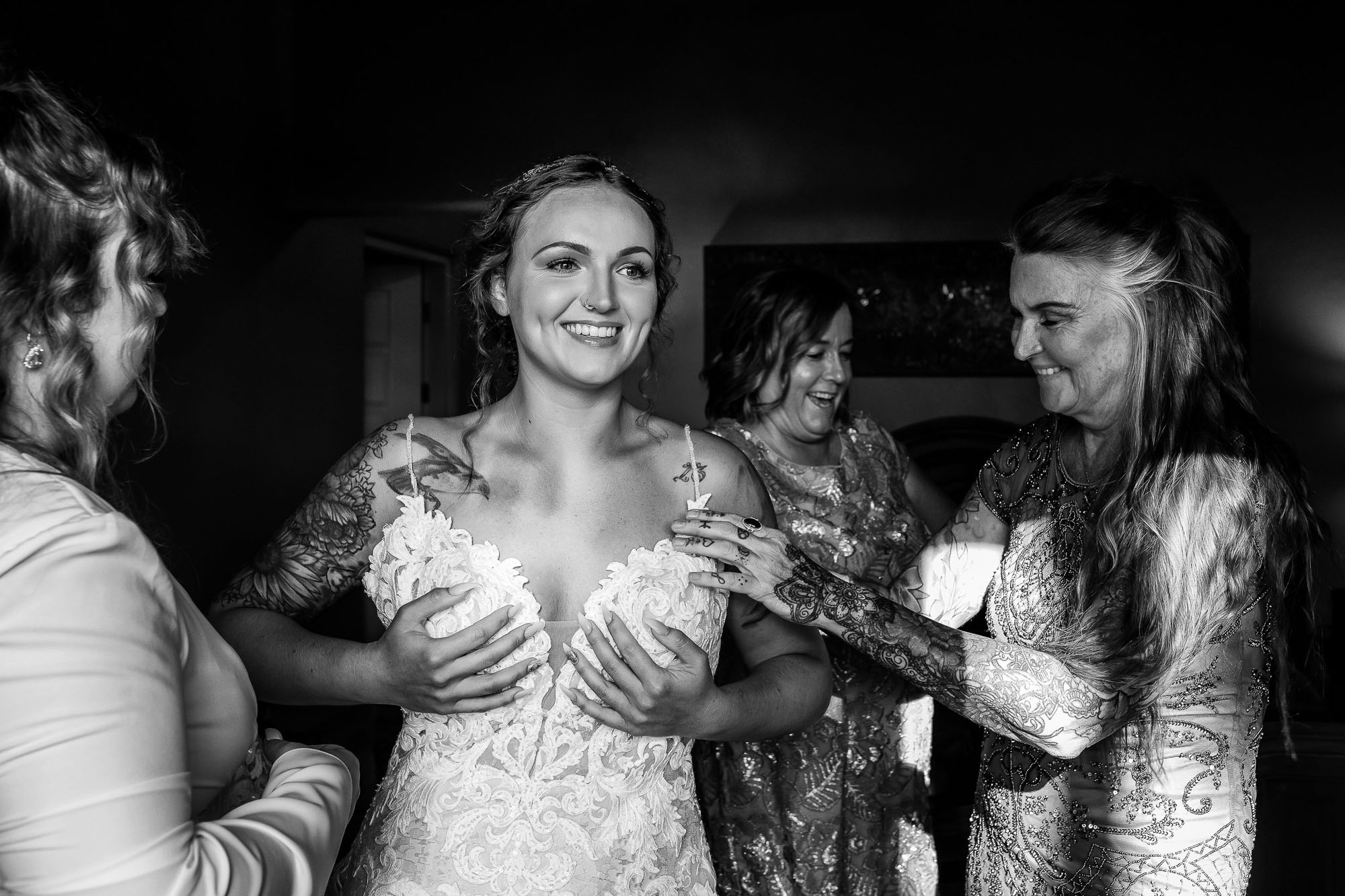 Tattooed bride being helped into her dress