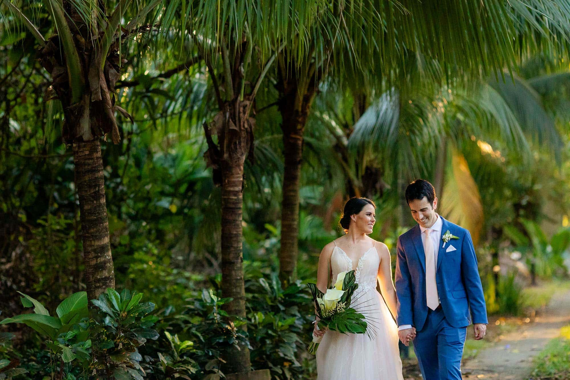 Bride and groom walk along a jungle path